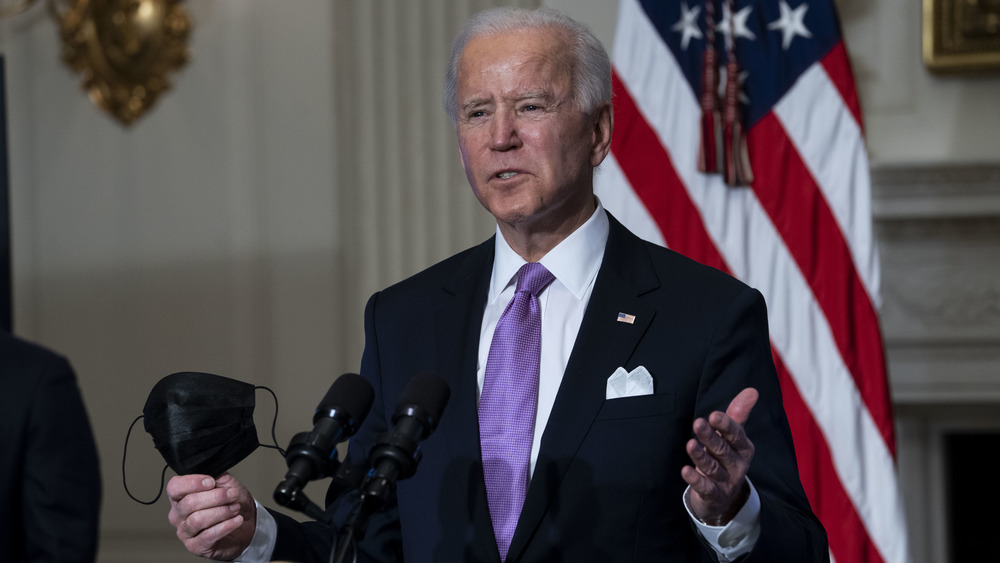 Joe Biden holding a face mask while speaking with reporters