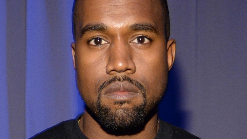 Kanye West poses in a black sweatshirt