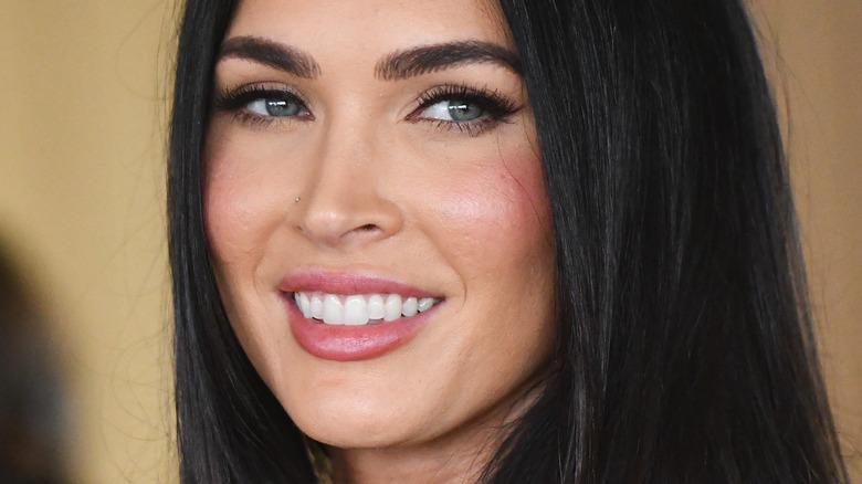 Megan Fox looks to side smiling