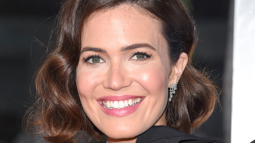 Mandy Moore looks sideways smiling into camera
