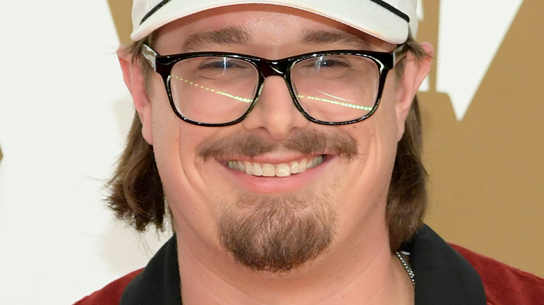 HARDY, smiling, on a red carpet, wearing glasses, wearing a white hat, facial hair