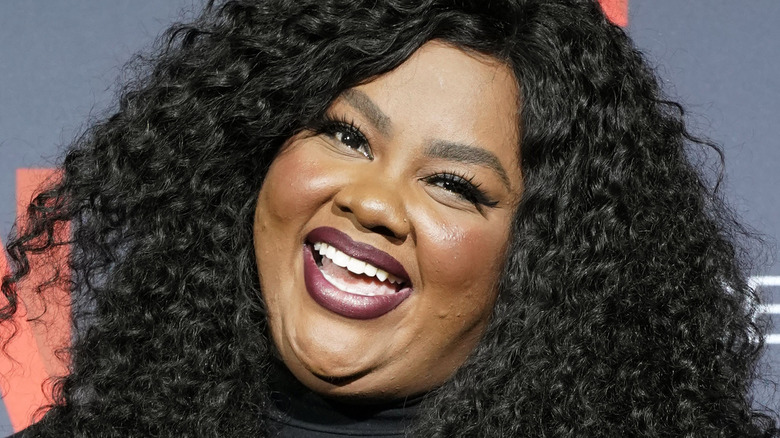 Nicole Byer smiling at a red carpet event