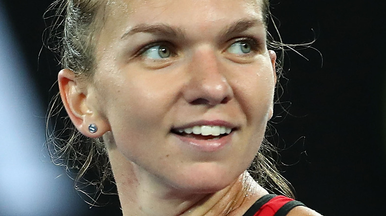 Simona Halep smiling and looking to the side while playing tennis