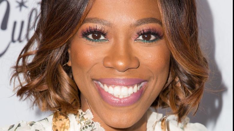Yvonne Orji smiling with colorful eye makeup