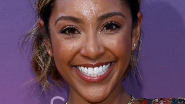 Tayshia Adams smiling at a red carpet event