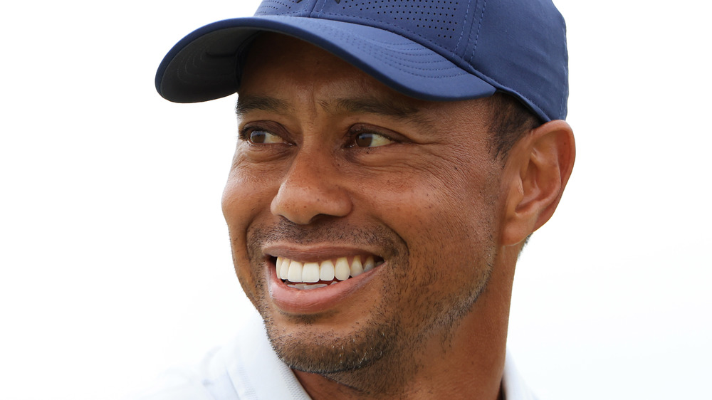 Tiger Woods smiles on a golf course