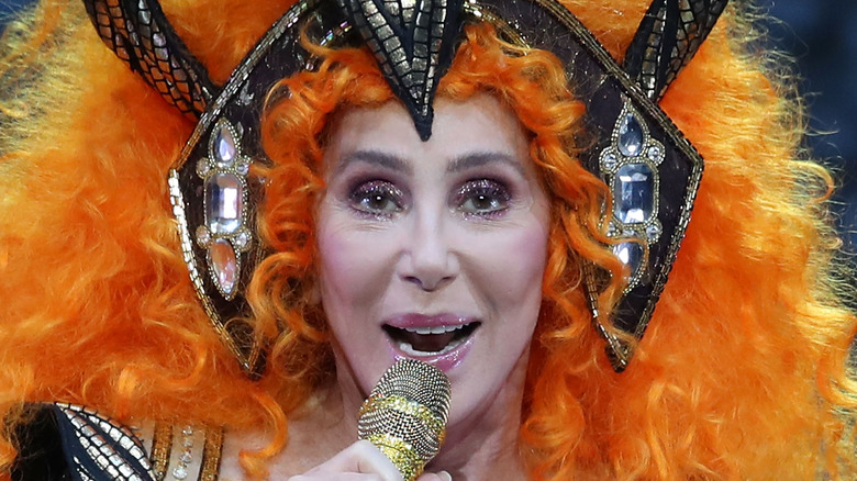 Cher in an orange wig, performing