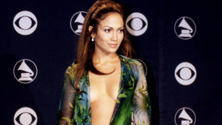 Jennifer Lopez smiles on the red carpet in green Versace dress