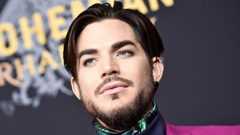 A bearded Adam Lambert looking stoic