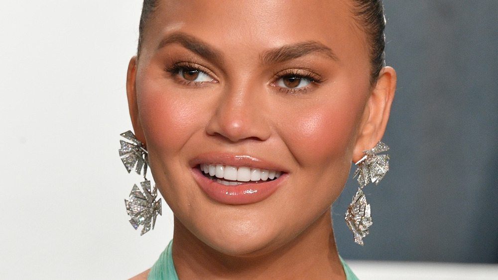 Chrissy Teigen poses and smiles