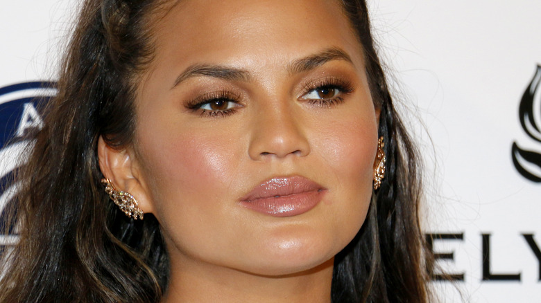 Chrissy Teigen with earclaws looking to the side