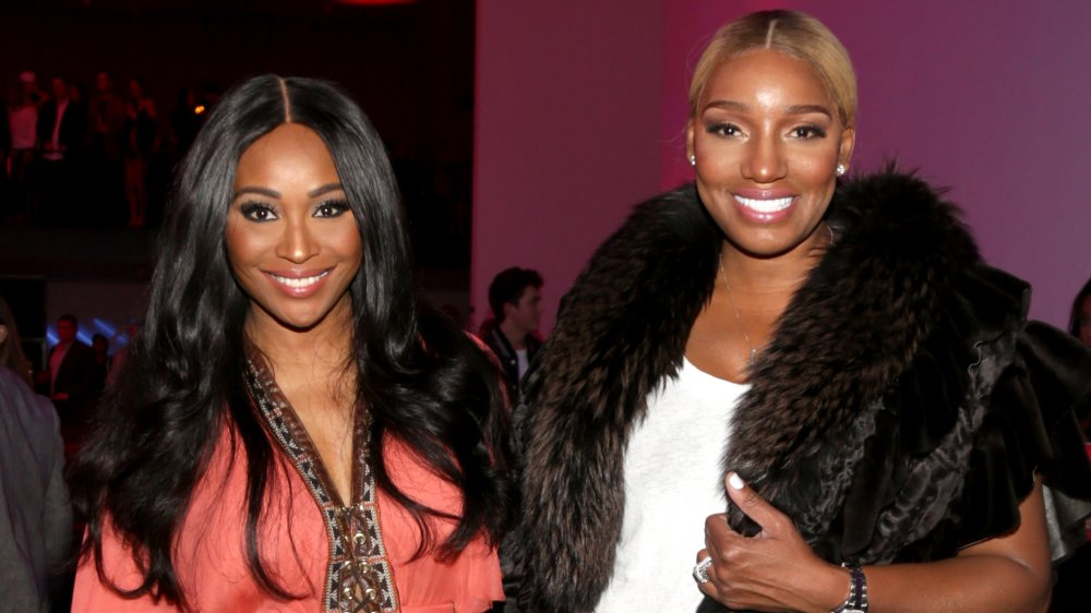 Cynthia Bailey and NeNe Leakes, smiling while posing arm in arm