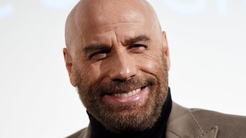 John Travolta smiles at a red carpet event