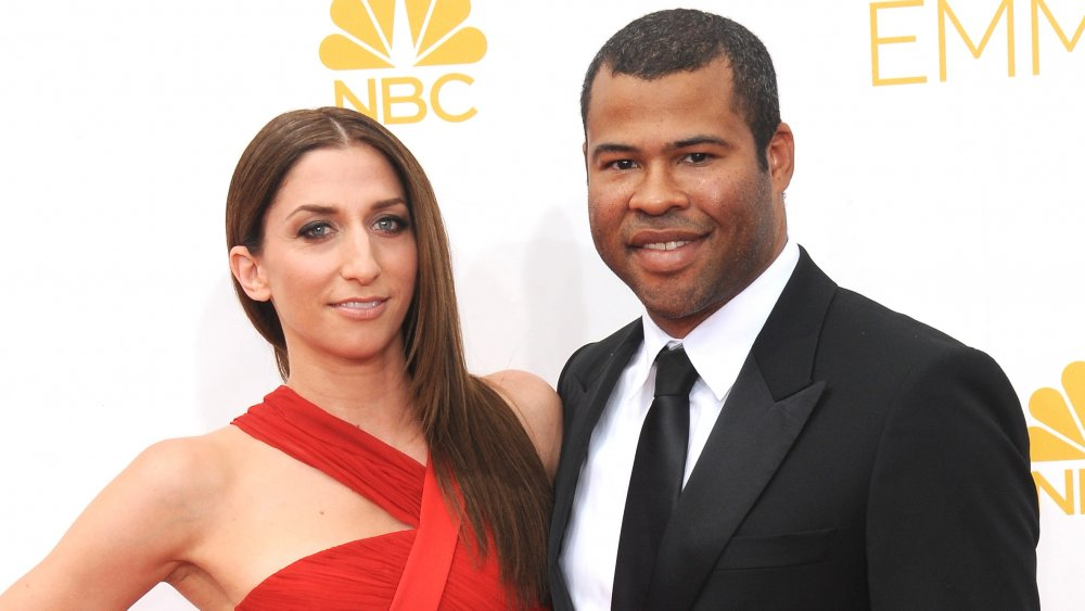 Chelsea Peretti in a red dress, Jordan Peele in a black suit, both smiling at the Emmys