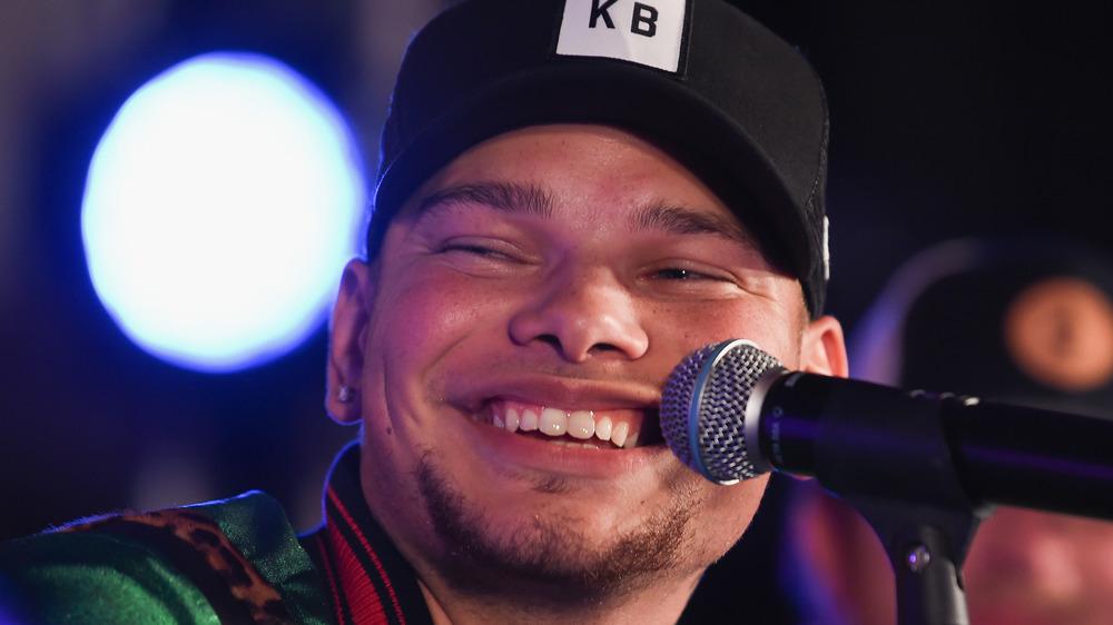 Kane Brown smiling behind microphone