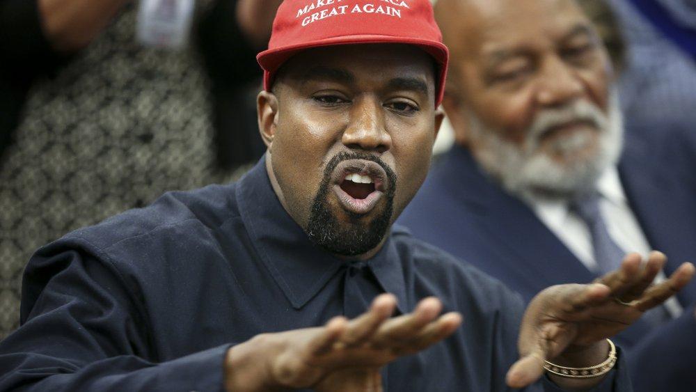 Kanye West wearing a MAGA hat, speaking