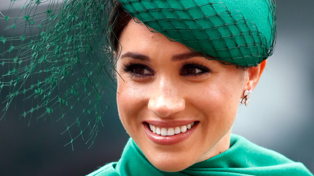 Duchess Meghan Markle smiles in a green hat