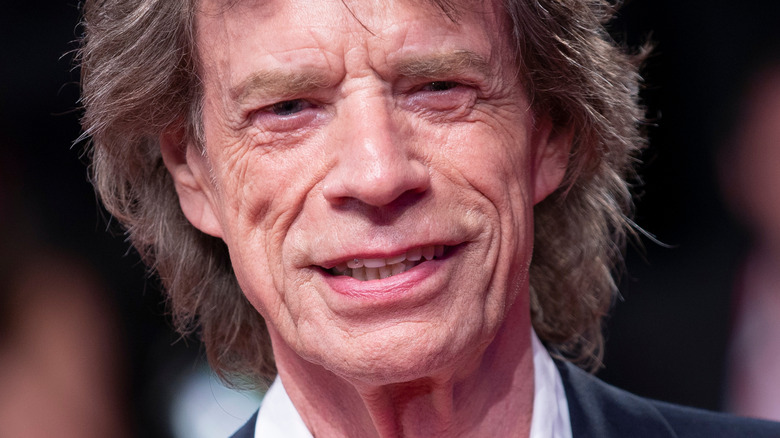 Mick Jagger smiling and wearing suit