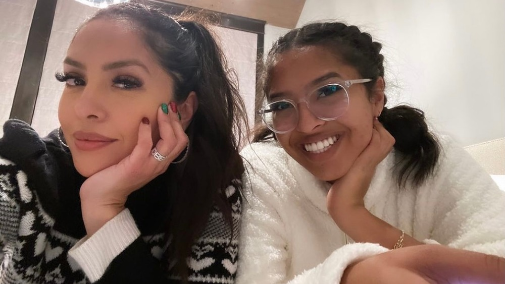 Vanessa Bryant in a pony tail and sweater taking a selfie, Natalia Bryant, smiling, in braids, in glasses