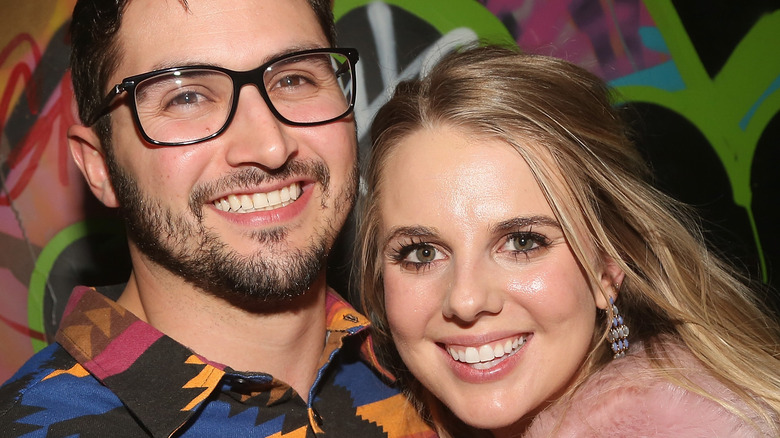 Victor Arroyo and Nicole Franzel smile and snuggle