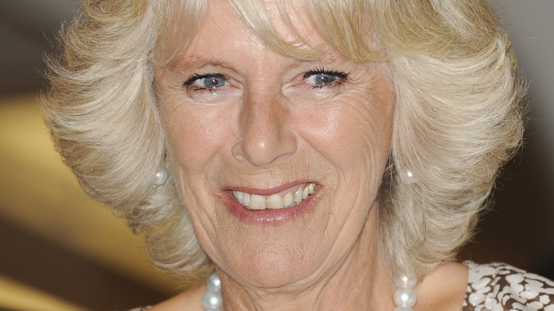 Camilla Parker-Bowles smiles wearing a pearl necklace.