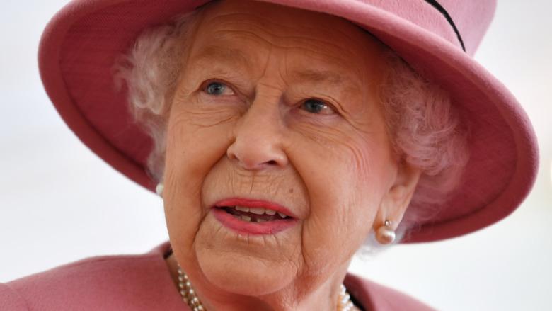 Queen Elizabeth II wears a pink hat