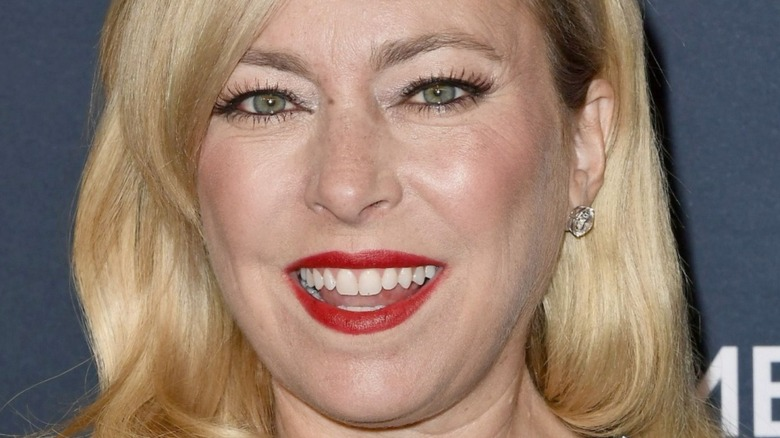 Sutton Stracke with wide smile and red lipstick