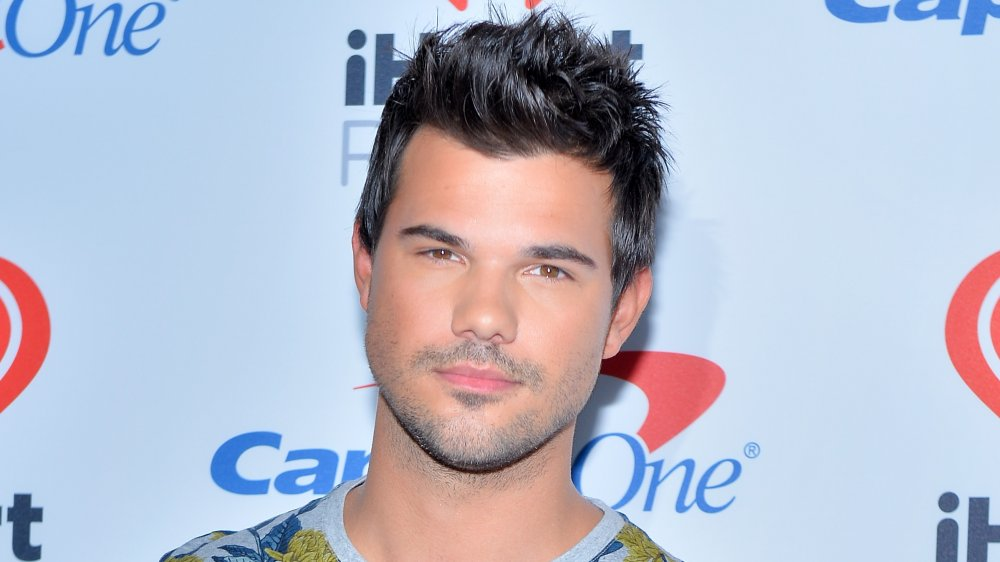 Taylor Lautner in a floral t-shirt, posing with a neutral expression at an iHeartRadio event