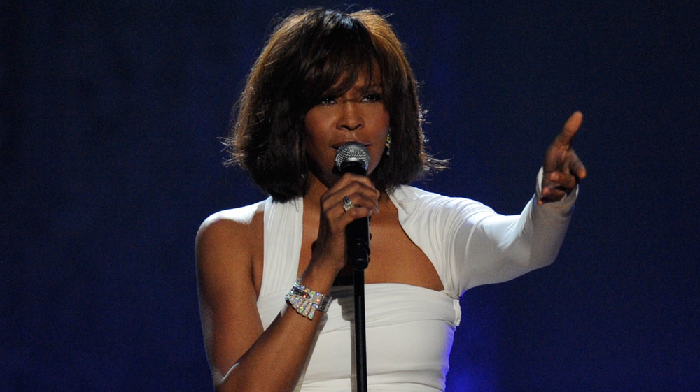 Whitney Houston raising hands on stage