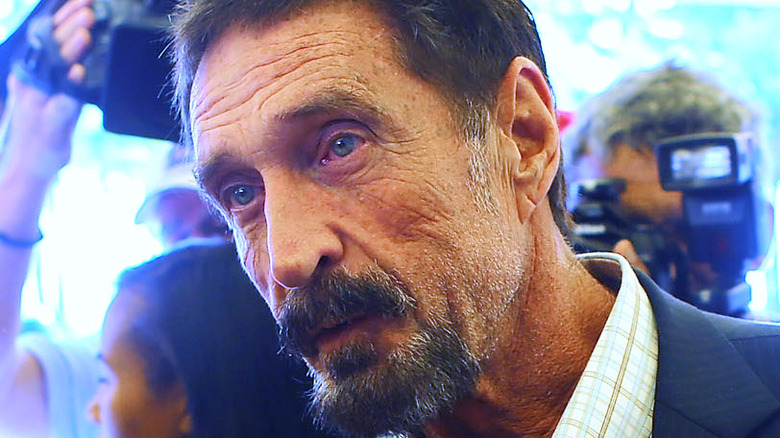 John McAfee in front of reporters