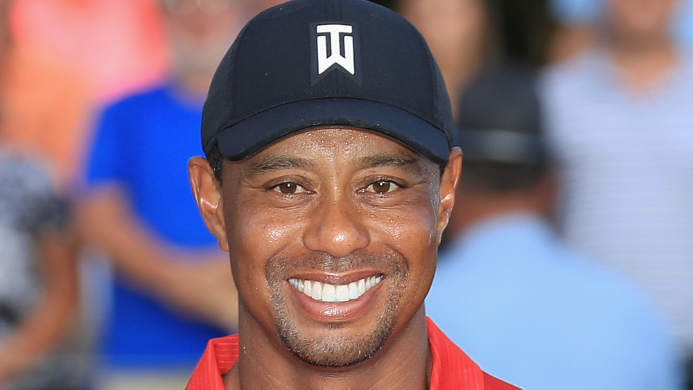 Tiger Woods smiling for photos on the golf course