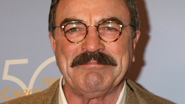 Tom Selleck with slight smile looking at the camera