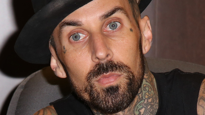 Travis Barker with serious expression and hat