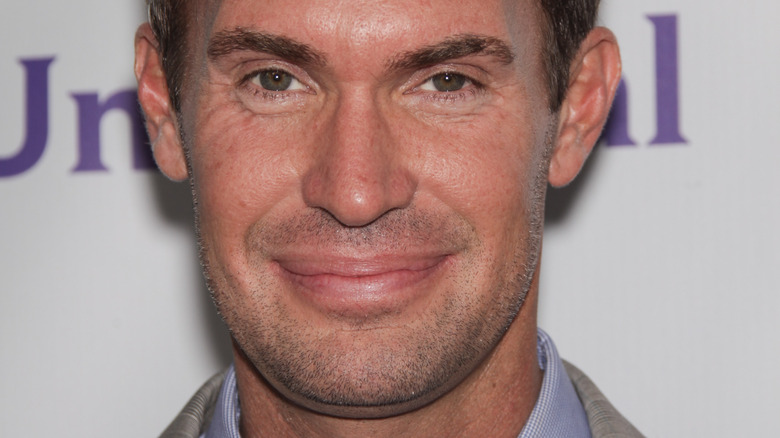 Jeff Lewis smirking and looking at camera while posing at an event