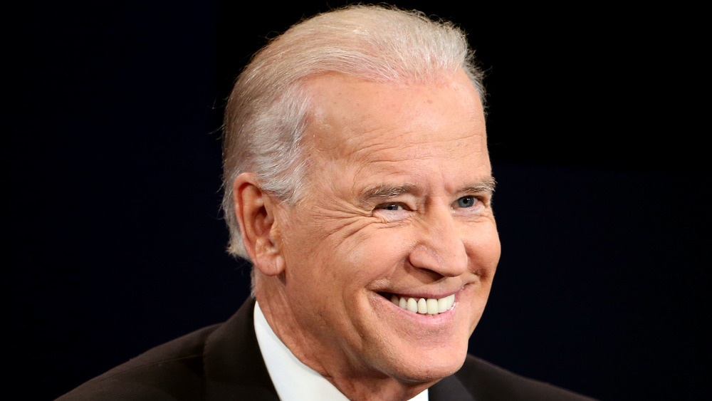 Joe Biden smiles while speaking at a conference