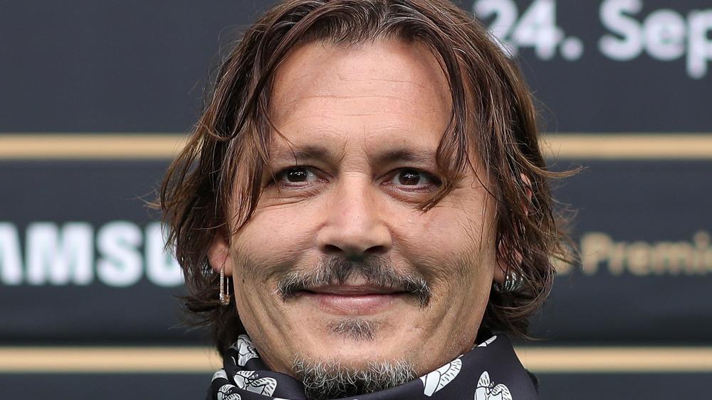 Johnny Depp smiling wearing earrings