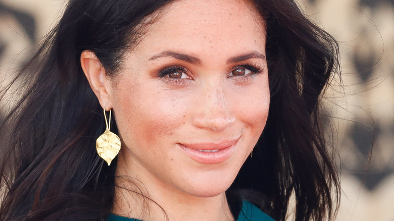 Meghan Markle poses in a green outfit.