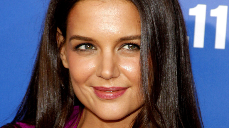 Katie Holmes in front of blue background