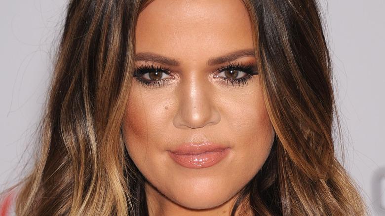 Khloe Kardashian smiles at an event