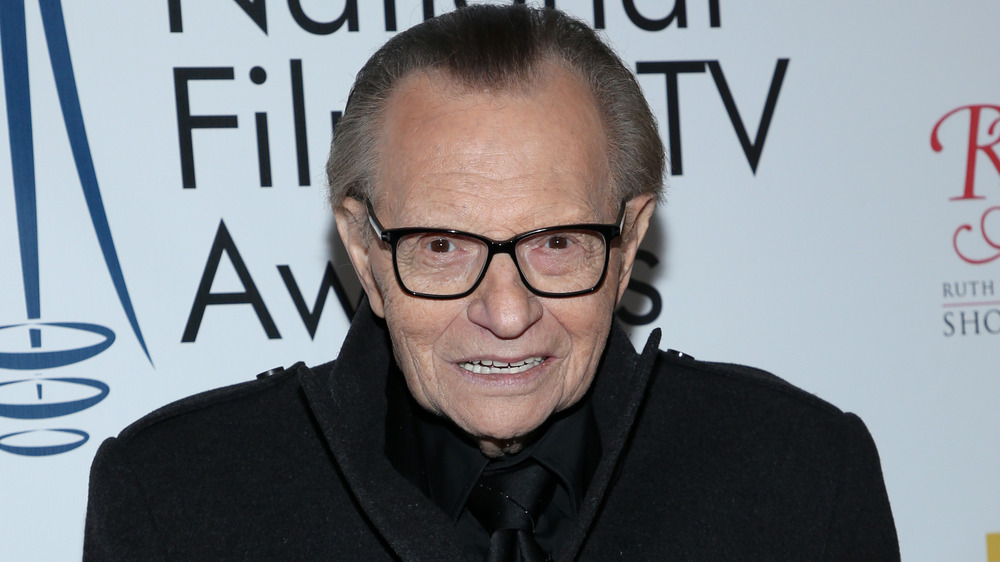 Larry King smiling on the red carpet