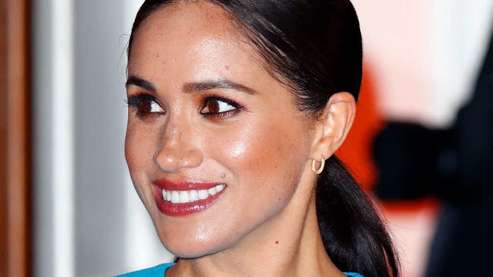 Meghan Markle smiles in red lip gloss and ponytail
