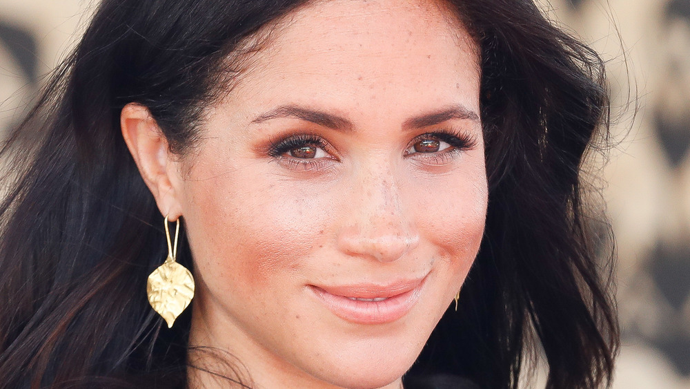 Meghan Markle smiling while wearing gold leaf earrings