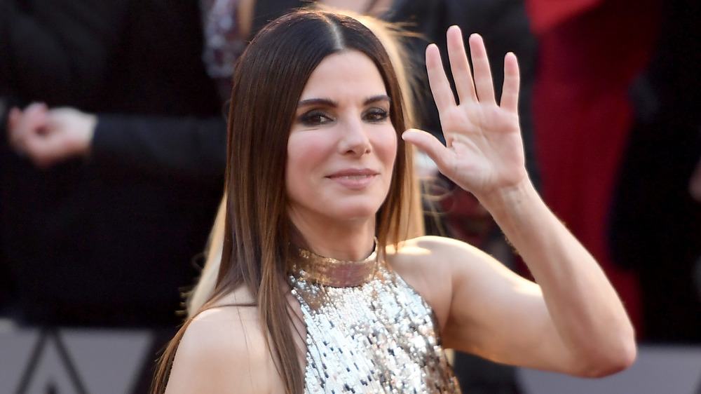Sandra Bullock walking and waving on red carpet