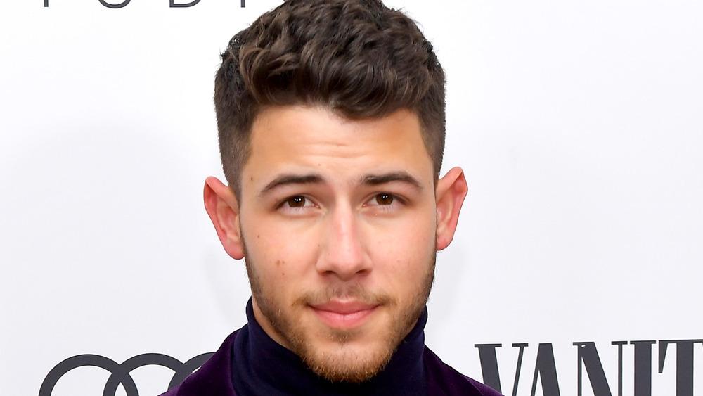 Nick Jonas posing for cameras smiling slightly