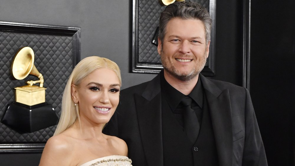 Gwen Stefani in a white dress, Blake Shelton in an all-black suit, both smiling at the Grammys