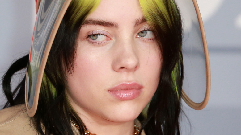 Billie Eilish in 2020 looking to side and wearing visor