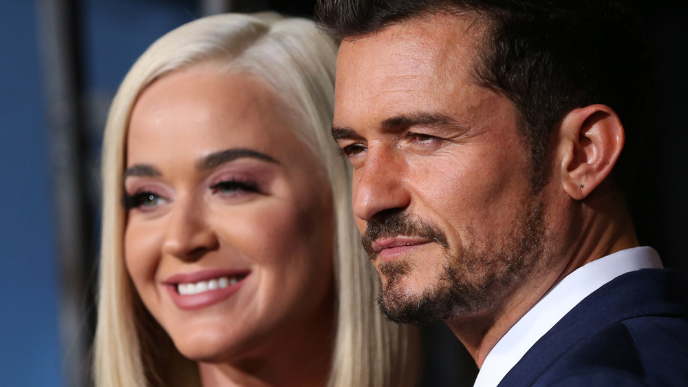 Katy Perry and Orlando Bloom smiling together at an event