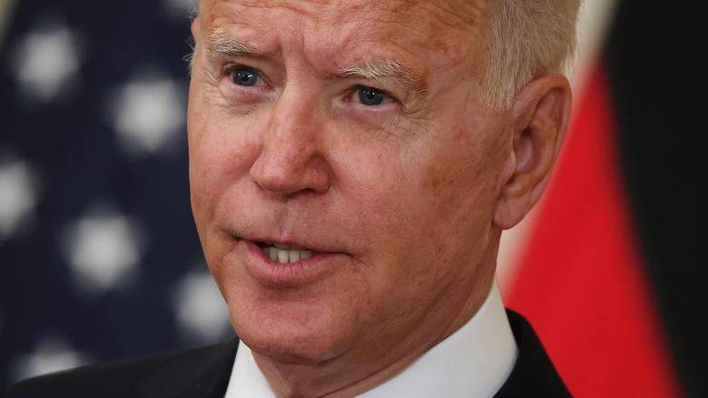Joe Biden speaking in front of American flag