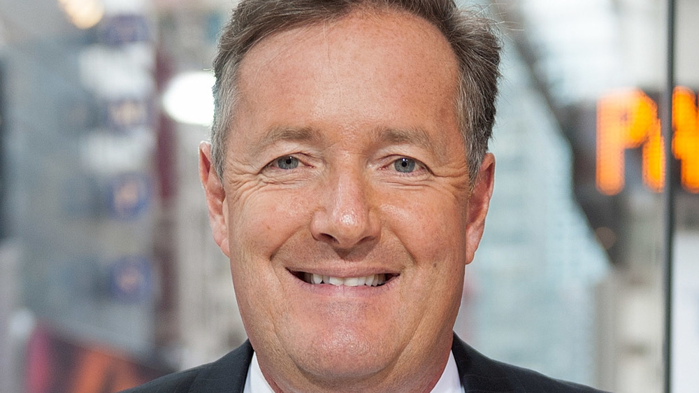 Piers Morgan grins at the camera while taking a photo-op in New York