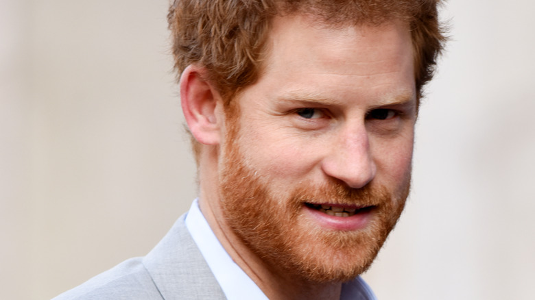 Prince Harry poses in a light gray suit.